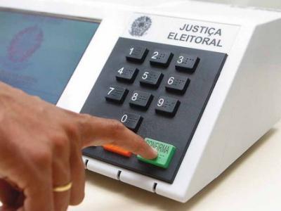 imagem mostra uma urna e um pessoa votando