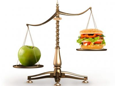 Imagem de uma balança pesando de um lado uma maça verde e de ouro um hambúrguer