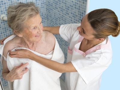 Imagem mostra idoso sendo auxiliado no banho