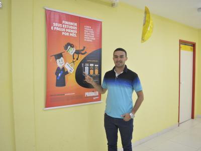 aluno sorri e aponta para banner com informações do educred