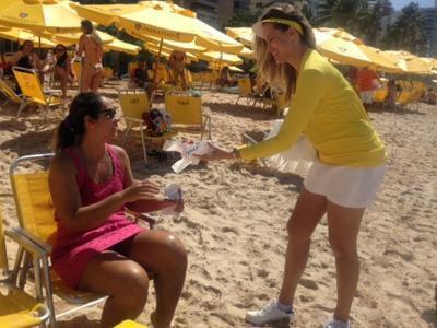 Imagem mostra estudante entregando sacolas na praia