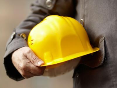 Imagem mostra trabalhador com capacete na mão