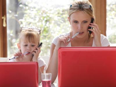 Imagem mostra mãe e filha fazendo uso de celular e computador
