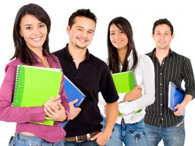 Imagem mostra alunos em pé segurando caderno
