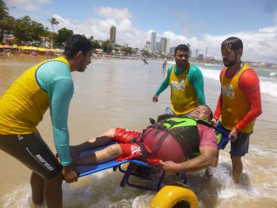 Imagem mostra alunos da UNINASSAU voltando do mar com um dos participantes