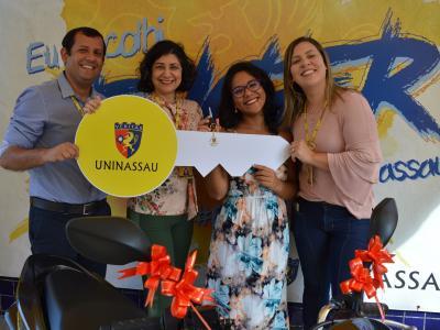 Imagem mostra entrega do prêmio para vencedora e participação de funcionários da UNINASSAU
