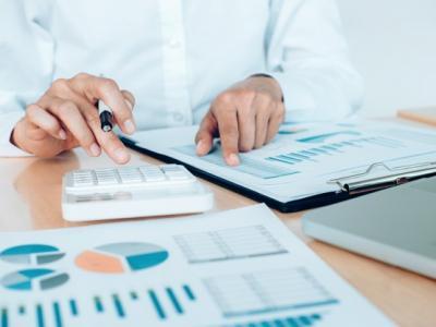 Imagem mostra pessoa na calculadora analisando documentos