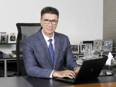 Imagem mostra Janguiê Diniz sentado à mesa e mexendo em um computador