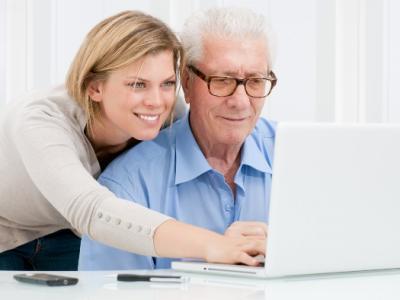 Imagem mostra um idoso e uma professora de informática