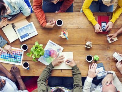Imagem mostra pessoas reunidas em uma mesa