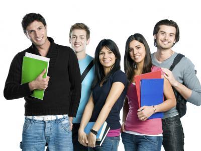 Imagem mostra estudantes em pé segurando caderno