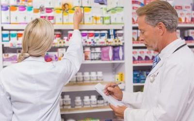 A imagem mostra um farmacêutico orientando uma farmacêutica