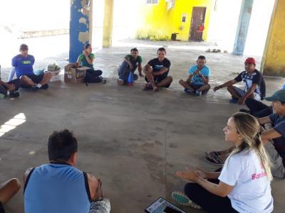 Imagem mostra pessoas sentadas no chão em uma roda de conversa