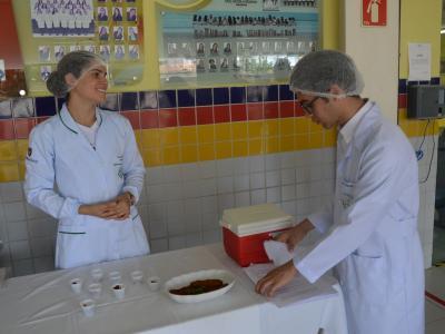 Imagem mostra estudantes apresentando o prato