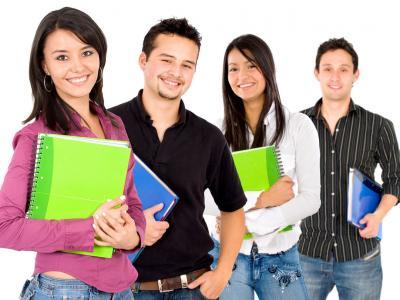 Imagem mostra estudantes em pé e segurando caderno