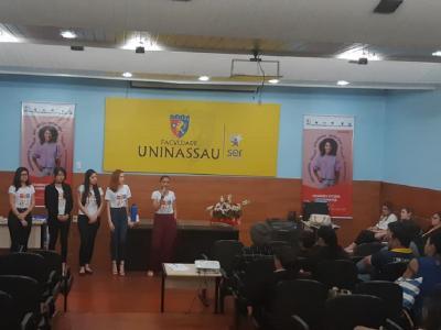 A imagem mostra cinco mulheres de pé participando do evento
