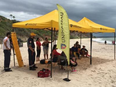 Toldos na praia com voluntários da ação