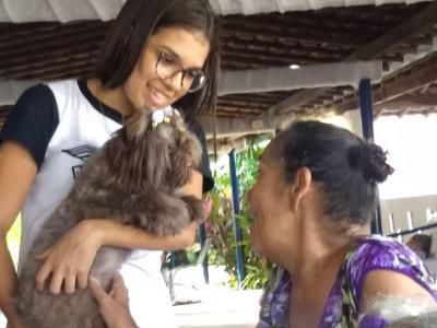 A imagem mostra uma idosa brincando com uma cadelinha que está no colo de uma aluna
