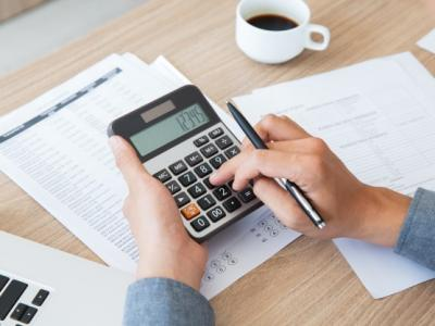 A imagem mostra as mãos de uma pessoa segurando uma calculadora e fazendo cálculos