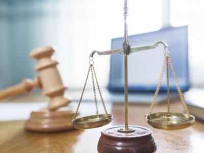 A imagem mostra uma balança e um malhete, símbolos da Justiça