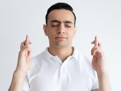 A imagem mostra um homem com uma camisa branca, fazendo sinal com as mãos