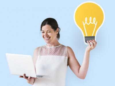 Mulher segurando ícone ideia e usando laptop