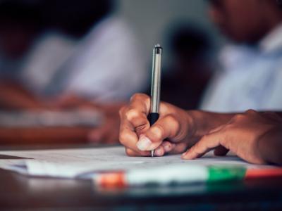 A imagem mostra uma pessoa escrevendo