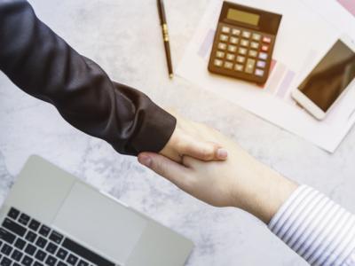 Imagem mostra colegas apertando as mãos acima da mesa
