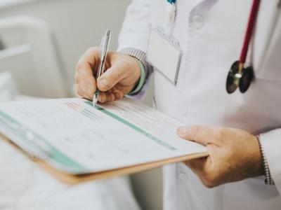 A imagem mostra um profissional de saúde fazendo anotações