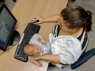 Imagem mostra mãe com bebê em frente ao computador