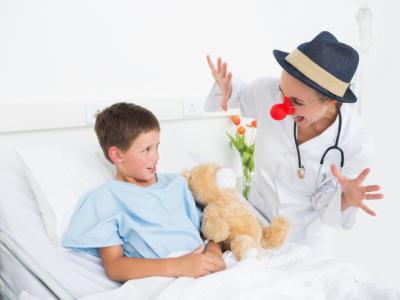 Imagem mostra palhaço conversando com paciente