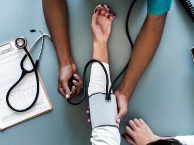 Imagem mostra enfermeira aferindo a pressão arterial de paciente