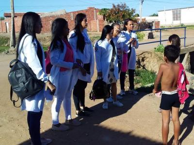 Imagem mostra estudantes orientando crianças na rua