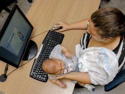 Imagem mostra mãe estudando no computador segurando criança