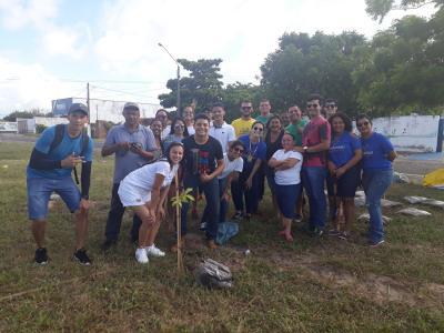 Imagem mostra alunos plantando árvore