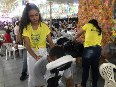 Imagem mostra duas alunas fazendo massagem em participantes