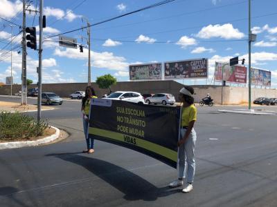 Imagem mostra estudantes enfaixadas e segurando um cartaz