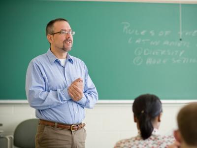 Imagem mostra professor em sala de aula