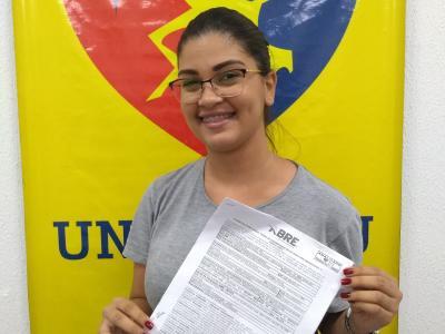 Imagem mostra aluna segurando contrato