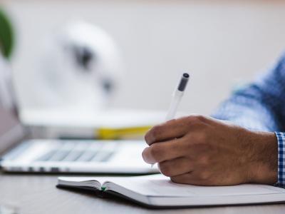 Mão escreve em caderno
