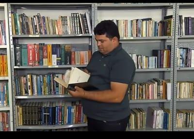Imagem mostra aluno lendo livro na biblioteca