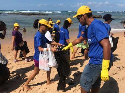 Imagem mostra pessoa coletando lixo na praia