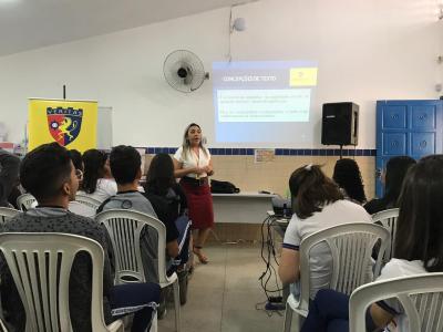 Imagem mostra professora dando aula para alunos