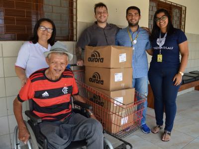 Imagem mostra colaboradores da UNINASSAU entregando donativos