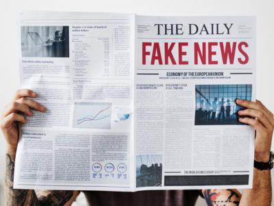 Imagem mostra mãos segurando jornal com manchete fake news