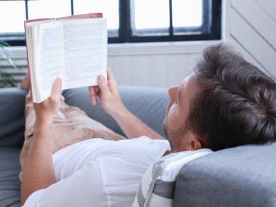 Imagem mostra homem lendo no sofá