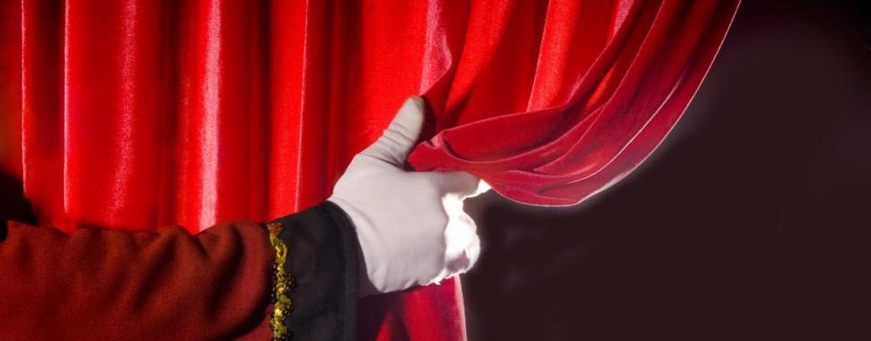 Imagem mostra uma mão abrindo a cortina do teatro