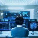 Imagem mostra pessoa em frente a computadores