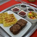 Imagem mostra waffle, brownie, salada de frutas e geleia