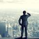 Imagem mostra homem em cima de edifício olhando cidade
